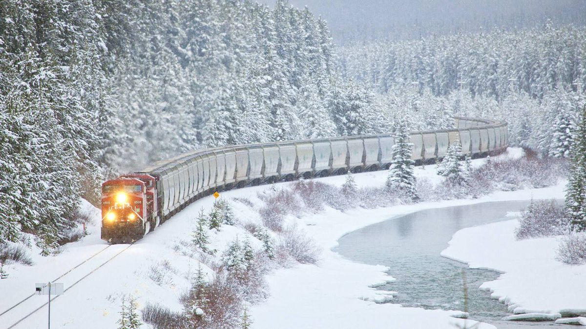 A Canadian Pacific train makes its way along the water's edge near Lake Louise, Alta.