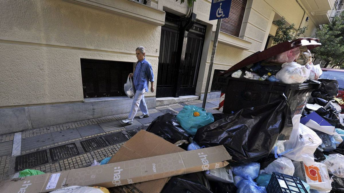 A woman walks past piles of garbage in Athens on October 14, 2011, on the eleventh day of a garbage collectors protest. Greece's two main unions said they would hold a two-day general strike next week against new austerity cuts by the government to address an unravelling debt crisis that has shaken the eurozone.