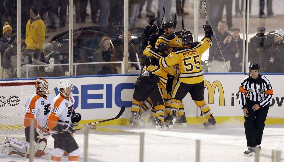 Teammates mob Boston Bruins' Marco Sturm after he scored the game-winning goal in against the Philadelphia Flyers in the New Year's Day Winter Classic NHL hockey game on an outdoor rink at Fenway Park in Boston, Friday, Jan. 1, 2010. The Bruins won 2-1 in overtime. (AP Photo/Charles Krupa)