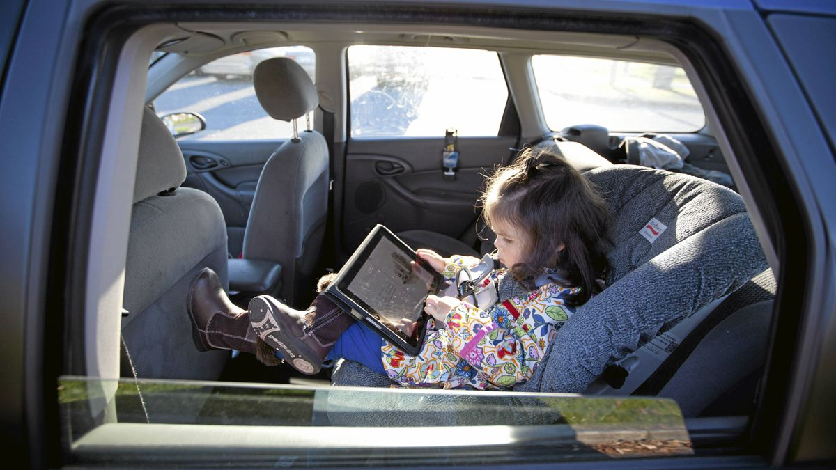 Olivia Lehmann, 3, sits in the back of her mom's car sitting in a child car seat playing on her fathers iPad in Richmond, B.C. November 3, 2010.