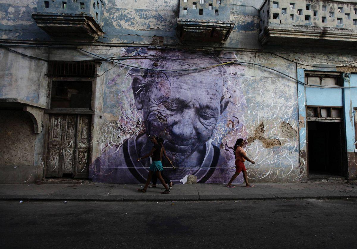 People walk beside a creation by Cuban-American artist Jose Parla and French artist J.R. on a street wall in Havana.