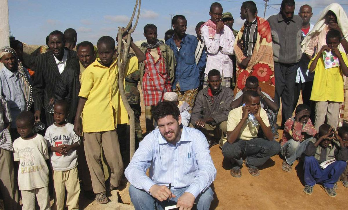 Canadian author Jay Bahadur poses with Somali villagers in Dhanane, the semiautonomous region of Puntland, Somalia, on June 1, 2009, while researching his book about piracy.