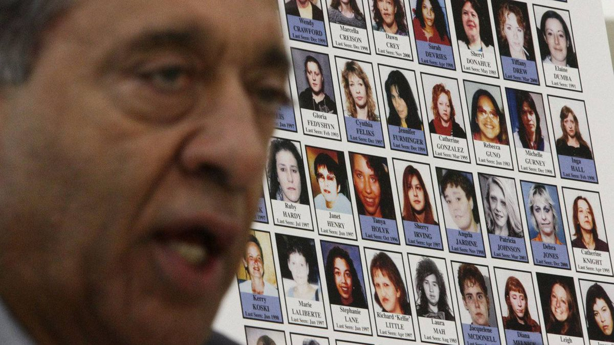 Photographs of missing women are displayed as Commissioner Wally Oppal speaks during the Missing Women Commission of Inquiry public forum in Vancouver, B.C., on Wednesday January 19, 2011.