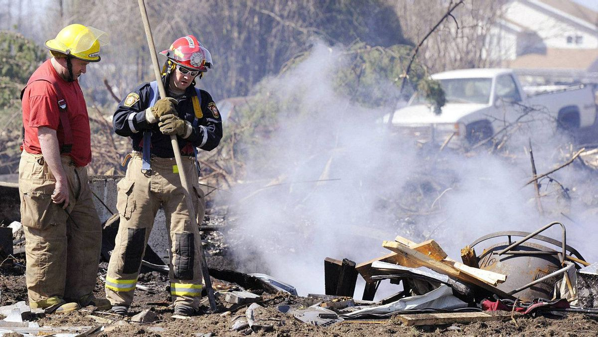Fire-fighters from the High Level fire department look for hot spots near a destroyed home near downtown Slave Lake, Alberta May 16, 2011.