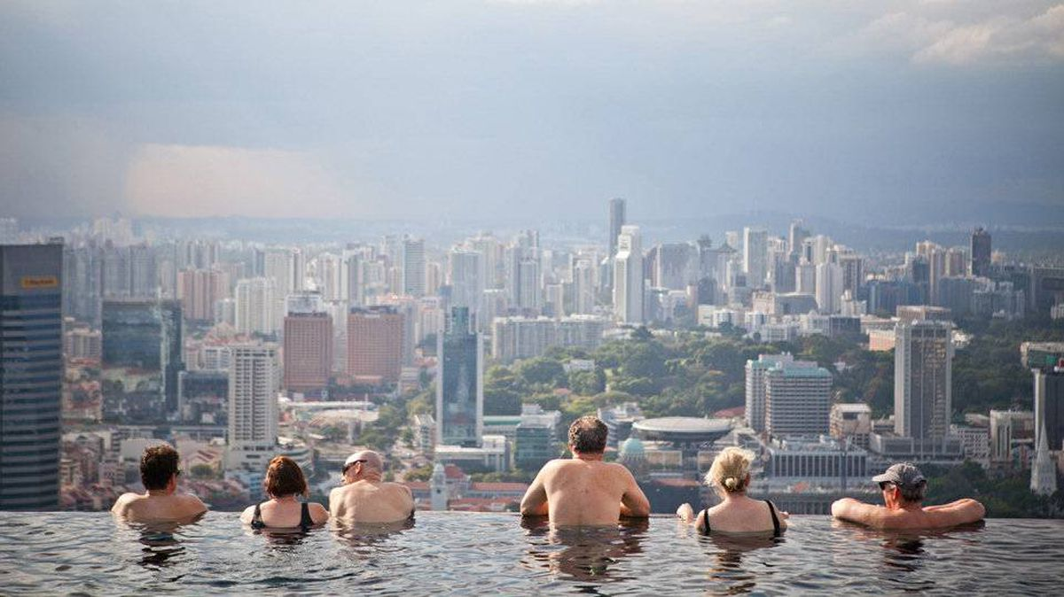 Hotel guests in the Marina Bay Sands infinity pool take in the city skyline.
