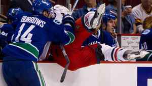 Vancouver Canucks' Alex Burrows, left, checks Columbus Blue Jackets' Fedor Tyutin, of Russia, during the first period of an NHL hockey game in Vancouver, B.C., on Tuesday November 29, 2011. The Canucks won 4-1. THE CANADIAN PRESS/Darryl Dyck