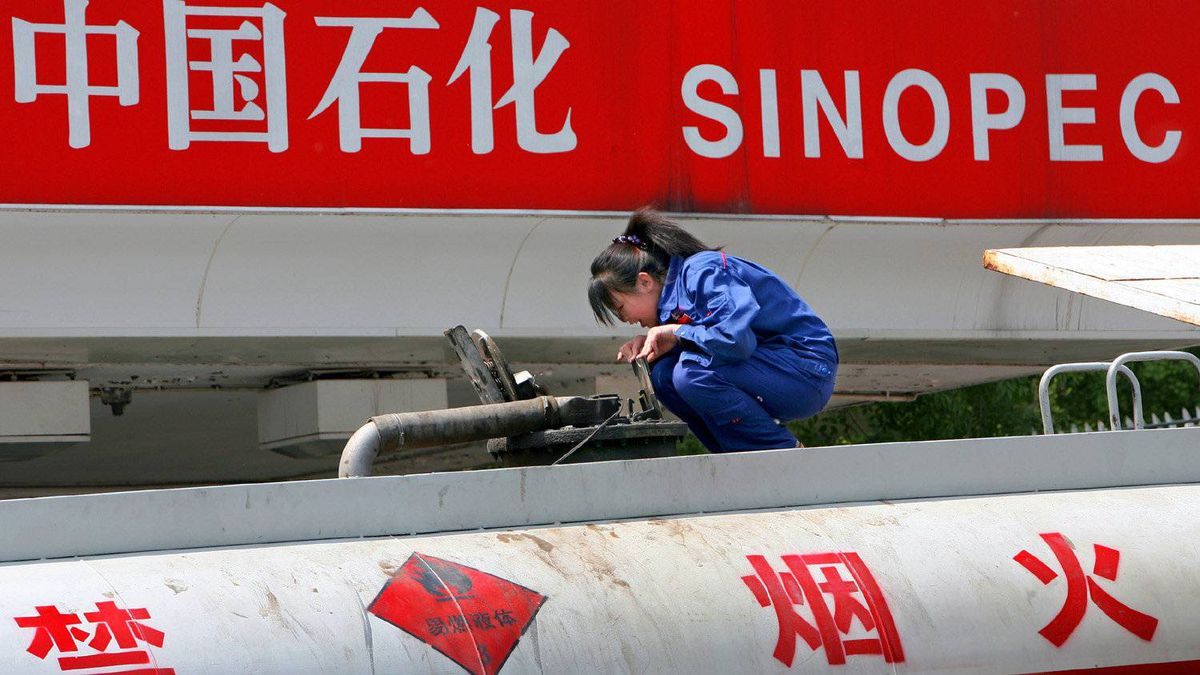 A Chinese worker checks a fuel tank at a Sinopec petrol station in Beijing, 26 April 2007.