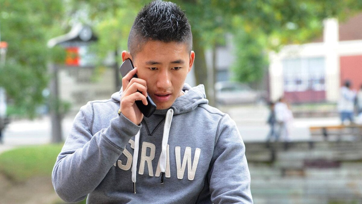 A Toronto student uses his cellphone.