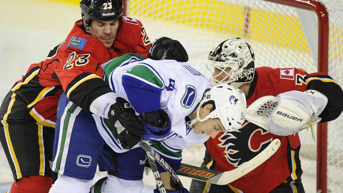 Calgary Flames' Scott Hannan (L) pushes Vancouver Canucks' Aaron Volpatti (C) out from in front of Flames' goalie Miikka Kiprusoff during the second period of their NHL hockey game in Calgary, Alberta, November 1, 2011. REUTERS/Todd Korol