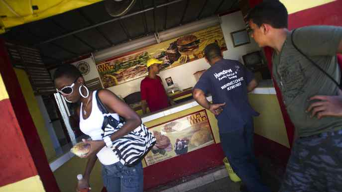 Cubans wait to order their meals at Tio Tito in Havana, Cuba Sept. 27, 2011. Taking its colour scheme from American fast food giant McDonald's the small restaurant is one of many that have opened up since recent economic reforms in Cuba have allowed for some private enterprise to exist.