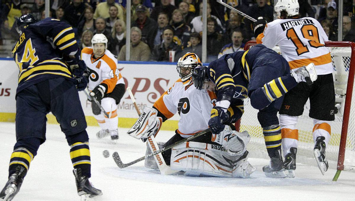 Buffalo Sabres' Chris Butler (34) shoots on Philadelphia Flyers goalie Brian Boucher as Sabres' Drew Stafford (21) is checked by Flyers' Scott Hartnell (19) during the first period in Game 3 of a first-round NHL Stanley Cup playoffs hockey series, in Buffalo, N.Y., Monday, April 18, 2011. (AP Photo/David Duprey)