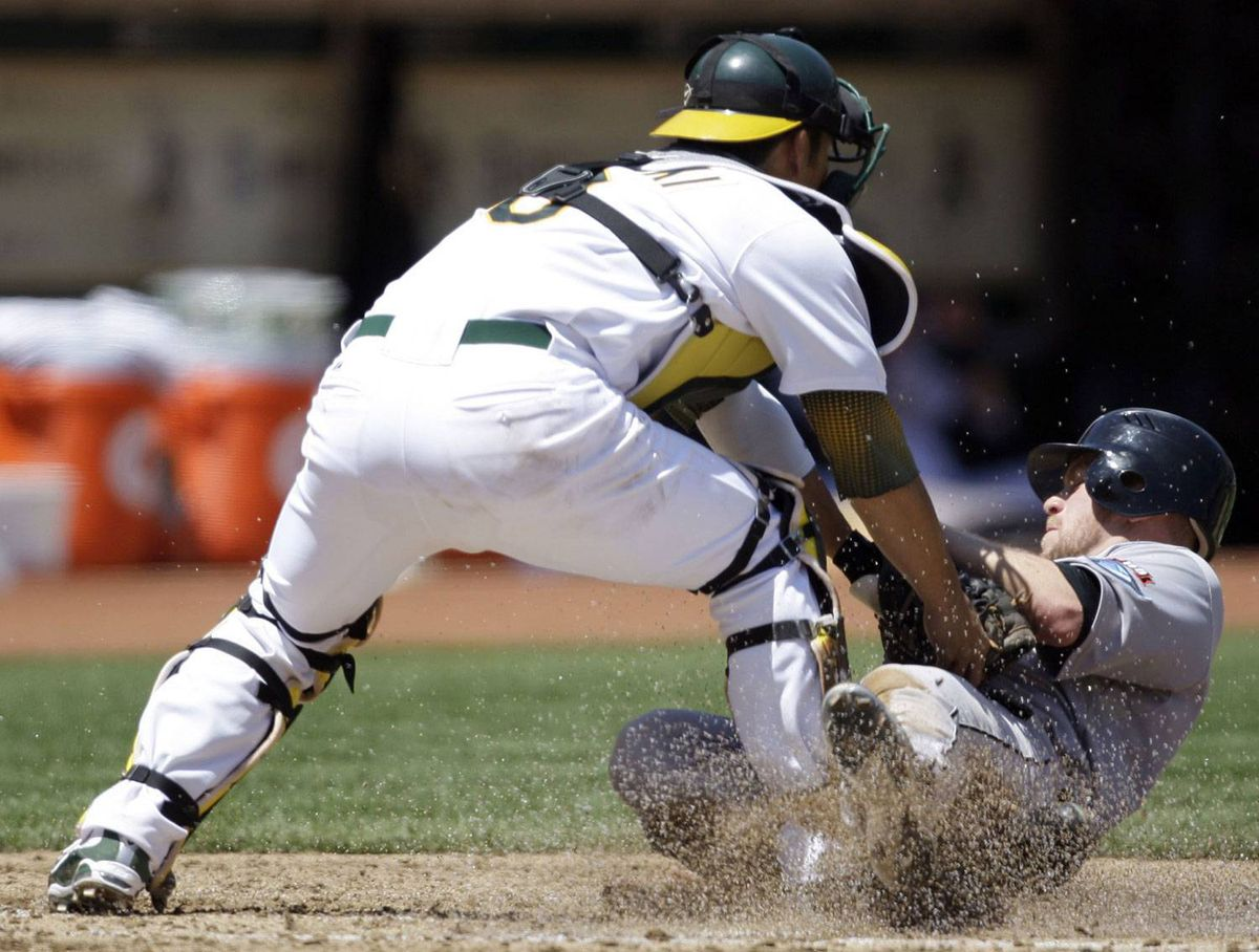 Toronto Blue Jays' Aaron Hill is tagged out by Oakland Athletics catcher Kurt Suzuki in the second inning of a baseball game Sunday, Aug. 2, 2009, in Oakland, Calif. Hill was attempting to score on a base hit by Vernon Wells. (AP Photo/Ben Margot)