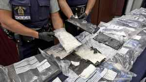 RCMP officers display cocaine after a drug bust in Montreal, June, 2010.