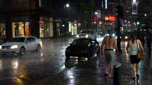James Lazar photo: July 21, 2011 - A walk In the Montreal rain. While most people sought shelter from the rain, this couple chose to enjoy the reduced traffic on the sidewalk. Serious Montrealers are not deterred from the nightlife by a bit of rain!
