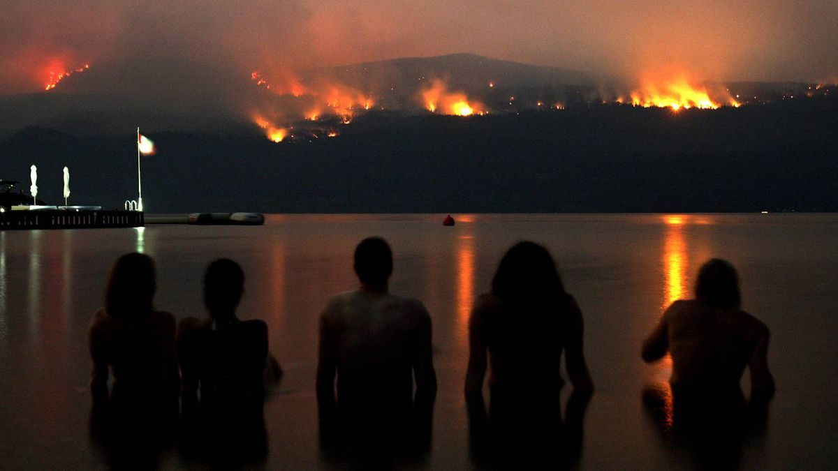A group of friends sit in Lake Okanagan as they watch wildfires burn on Terrace Mountain north of Kelowna, B.C., in the early morning hours of Tuesday.