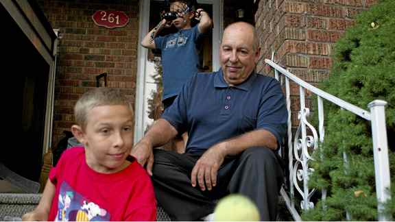 Blair Dimock (right) sits on the steps of his Toronto home with his twin thirteen year old sons Cameron (left) and Malcom (centre) on Sept. 13, 2011.