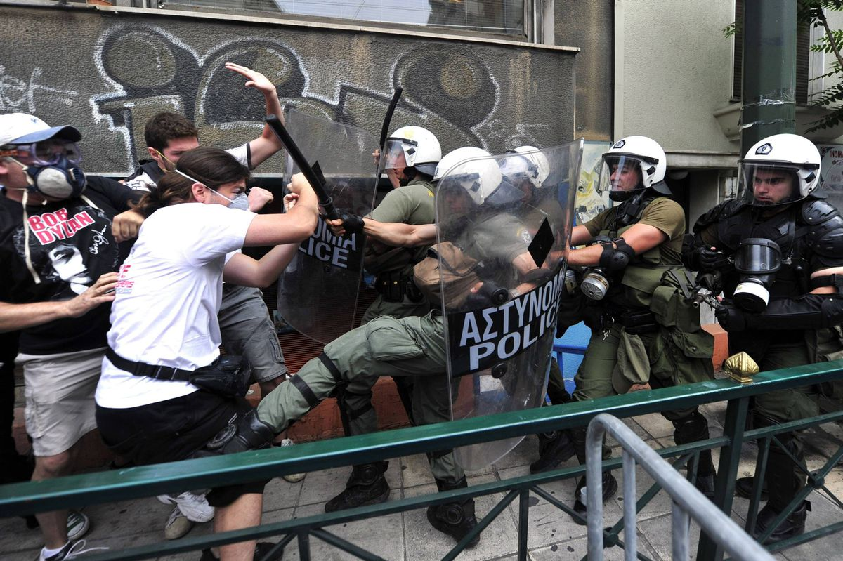 Protestors clash with riot police during a 48-hour general strike in Athens on June 29, 2011. Protestors clashed with police, who fired tear gas early on June 29, several hours before the Greek Parliament was to vote on an austerity package. The vote on a 28.4 billion-euro (40.8 billion US dollar) package of taxes, spending cuts and sell-offs is crucial for Greece to secure international aid to stave off bankruptcy, which is threatening the stability of the eurozone. AFP PHOTO / ARIS MESSINIS (Photo credit should read ARIS MESSINIS/AFP/Getty Images)