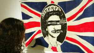 """A visitor to the """"Punk: A True and Dirty Tale"""" exhibition in central London looks at one of the most famous images from punk band the Sex Pistols, Wednesday Oct. 6, 2004. The Sex Pistols are set to re-release their controversial album in time for the Queen's jubilee in 2012."""