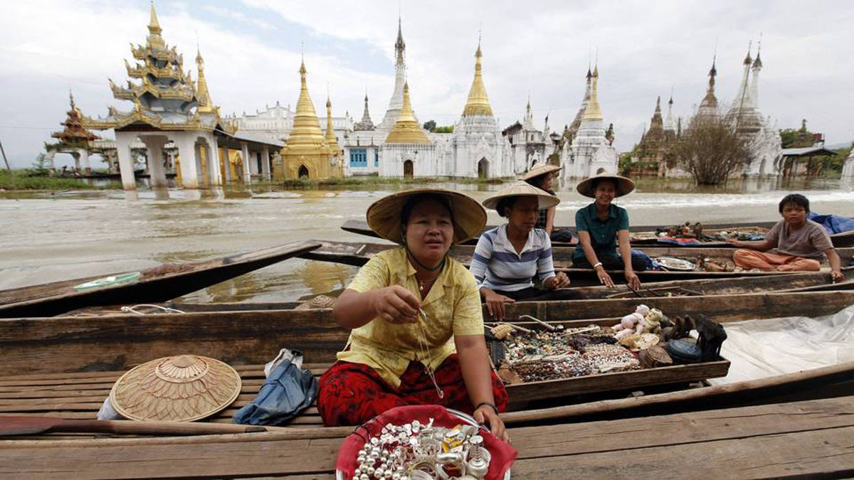Women sell souvenirs from small boats near Ywarma floating Pagoda in Inle Lake, Myanmar.