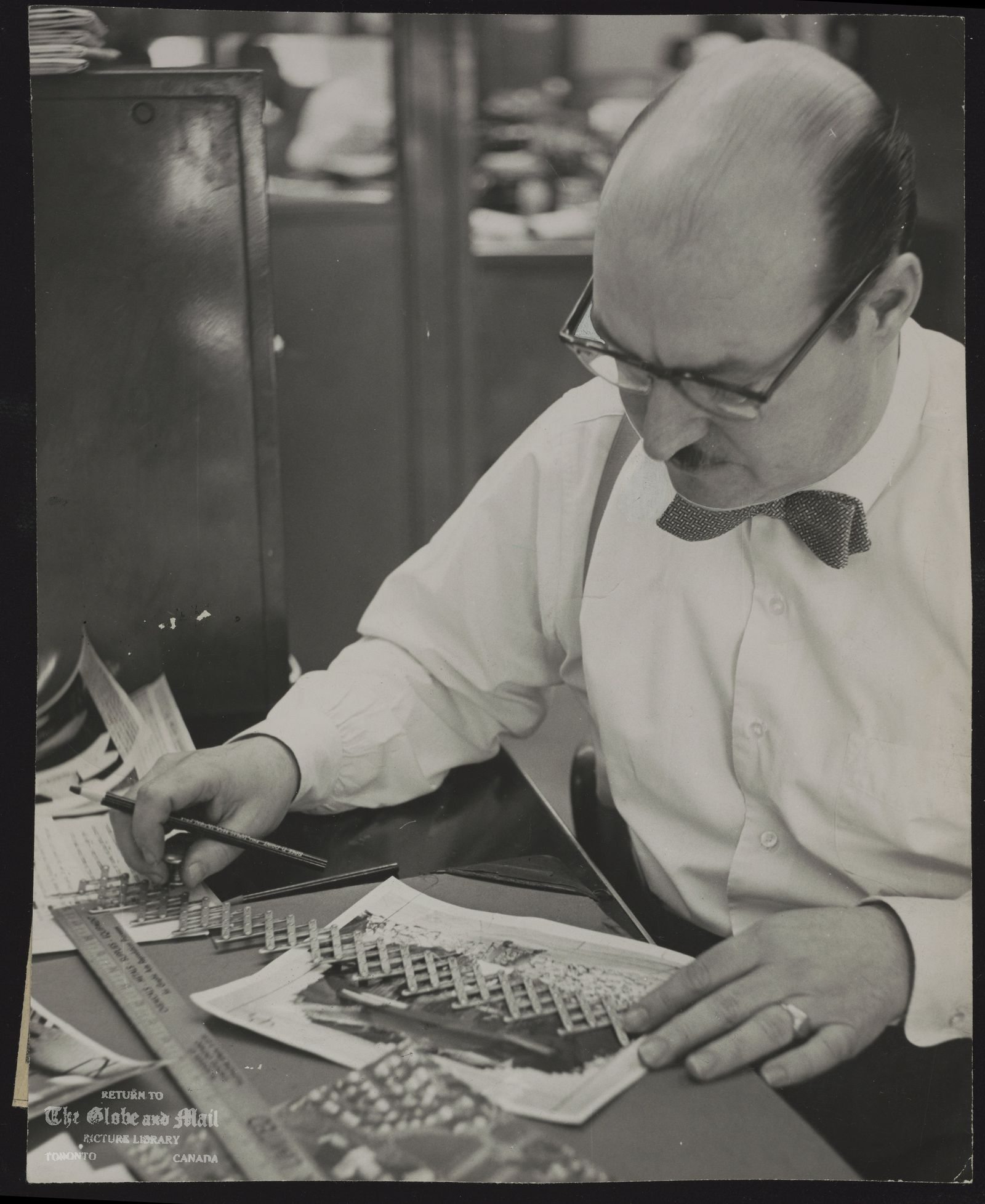 Norman D. BARRON Toronto. Newspaperman. Globe and Mail Assistant Photo Editor Norman Barron using a pantograph. Layout expert served 41 years with Globe. Norman Barron, a big, red- faced cigar-smoking extrovert who started his career as a copy boy at The Globe 41 years ago when he was 14, died of a heart attack early Saturday. As a result, his car struck a safety island and turned over on St. Clair Avenue East at Inglewood Drive. He was returning home from a party. The senior member of The Globe and Mail newsroom, Mr. Barron was responsible over the years for much of the makeup and design of the newspaper. He was considered by his colleagues at the three Toronto newspapers as the best in the business at solving layout problems. He joined The Globe in 1929 and in 1933 he became an apprentice printer and worked in the composing room of The Globe and later The Globe and Mail until he joined the army in 1940. He was stationed at Brantford and did not go overseas. In 1947 he transferred from the composing room to the editorial department as a make-up editor. It was an unusual move, the first such transfer at the paper. Ten years later he did the typographical design for the new Globe Magazine and Saturday weekly section of the newspaper. He was a gruff character who bellowed in complaint when a layout wasn't as he wanted it.