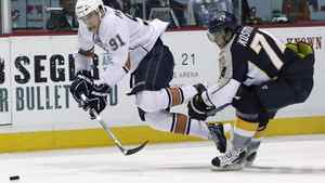 Edmonton Oilers left wing Magnus Paajarvi (91), of Sweden, falls as he chases the puck with Nashville Predators left wing Sergei Kostitsyn (74), of Belarus, in the second period of an NHL hockey game Tuesday, March 22, 2011, in Nashville, Tenn. Kostitsyn was called for tripping on the play.
