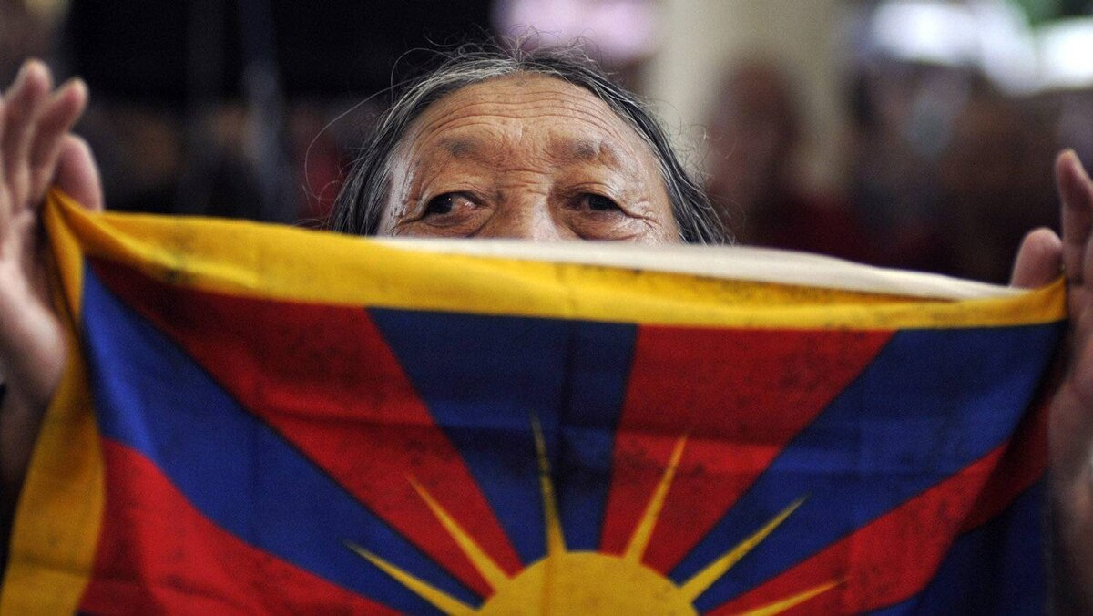 An elderly Tibetan woman holds a Tibetan national flag after the swearing-in ceremony.