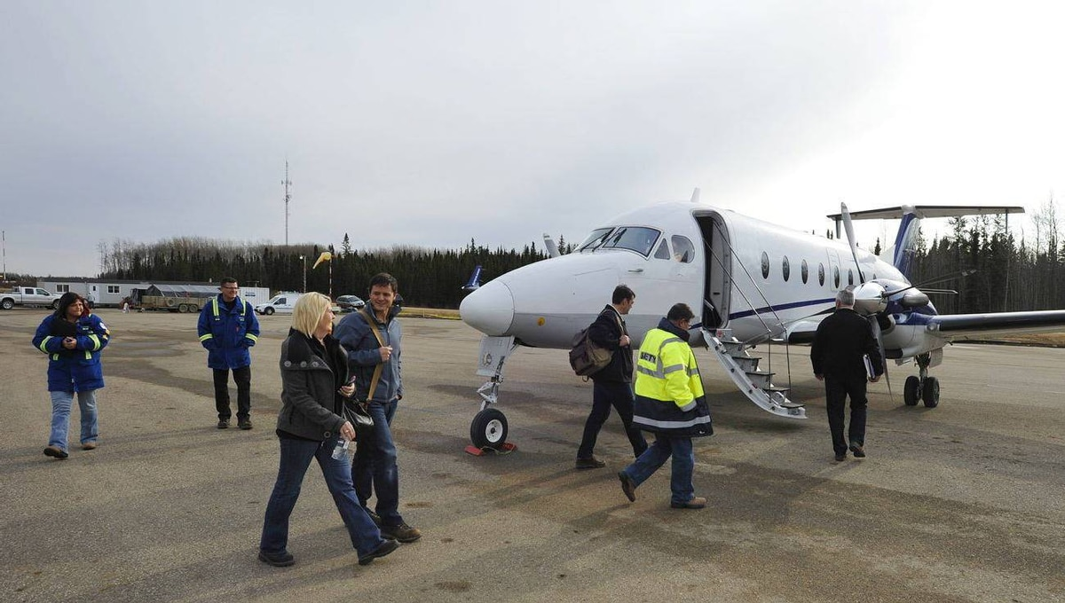 Staff from Devon Energy load a North Cariboo Aircraft at the company's modernized airport near Conklin, Alta.
