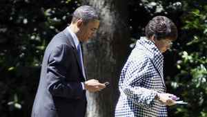 U.S. President Barack Obama checks his BlackBerry while walking with senior adviser Valerie Jarrett towards the Oval Office at the White House in Washington, May 4, 2010.