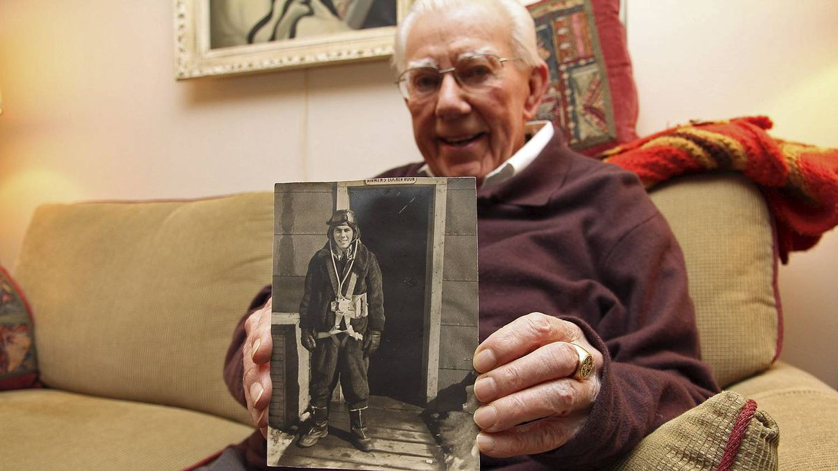 Don Cheney, age 89. holds a photograph of himself taken before a World War Two bombing mission.
