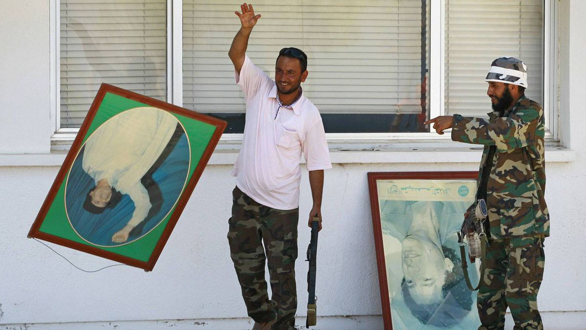 Rebel fighters destroy posters of Libyan leader Muammar Gadhafi which were found in the administrative centre of the Zawiyah oil refinery, Aug.18, 2011.