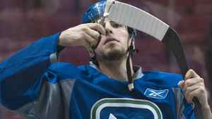 Vancouver Canucks Alex Burrows trims the tape on his stick during practice. REUTERS/Andy Clark