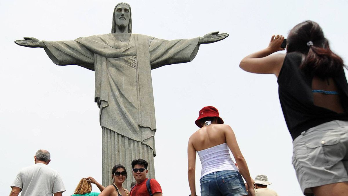 Tourists take picture in front of Brazil's most famous landmark, Christ, the Redeemer statue,