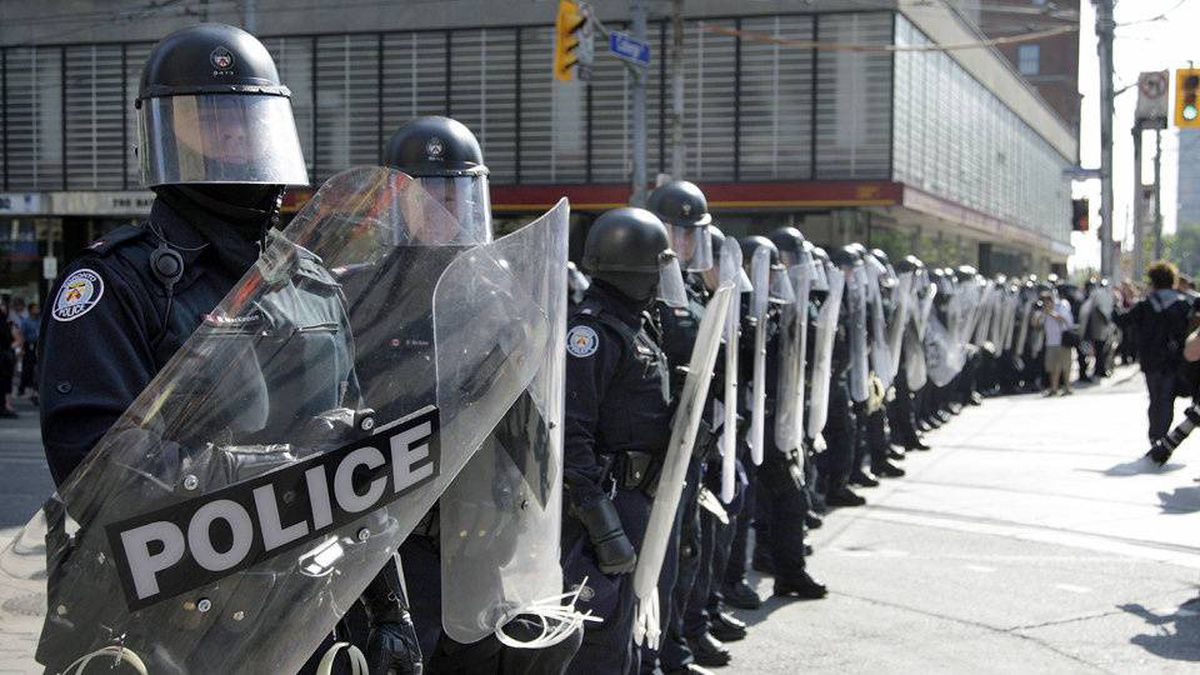 Police in riot gear stand on University Avenue at College Street to block an anti-G20 summit march in downtown Toronto on June 25, 2010.
