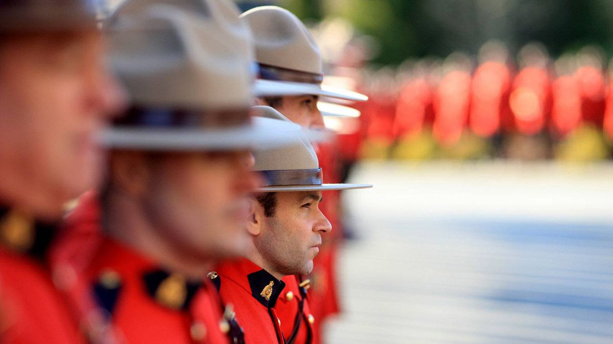 Mounties stand at attention waiting for the casket of RCMP civilian pilot Dave Brolin on January 26th, 2012.