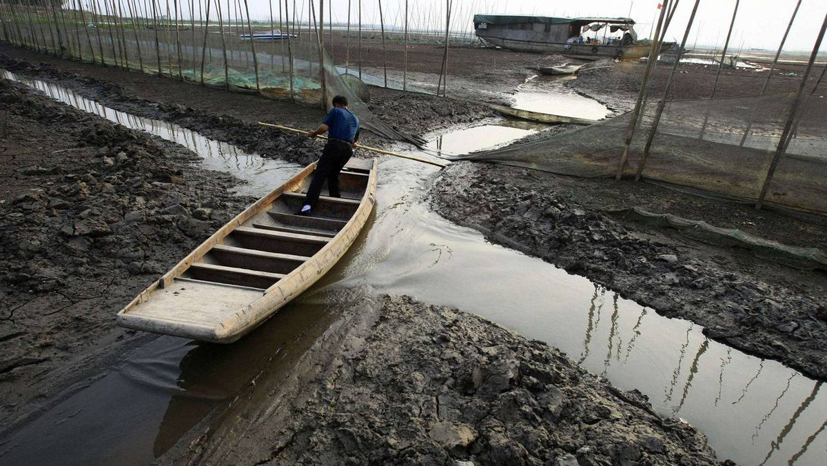 A fisherman tries to paddle his boat through a small stream amid the partly dried-up Honghu Lake in Honghu, Hubei province.