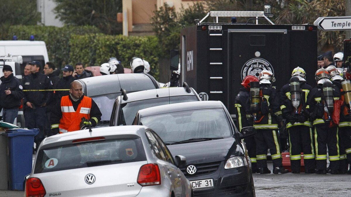 French special intervention police officers and firefighters are seen near the building under siege in Toulouse, on March 22, 2012.