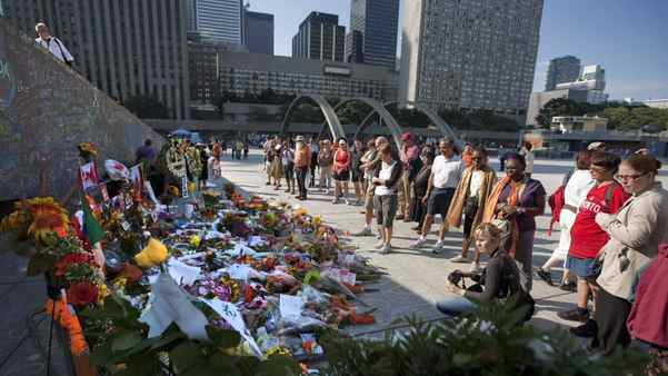 People pay their respects at a vigil for Jack Layton at Nathan Phillips Square prior to the funeral of the late NDP leader in Toronto on Saturday, August 27, 2011.