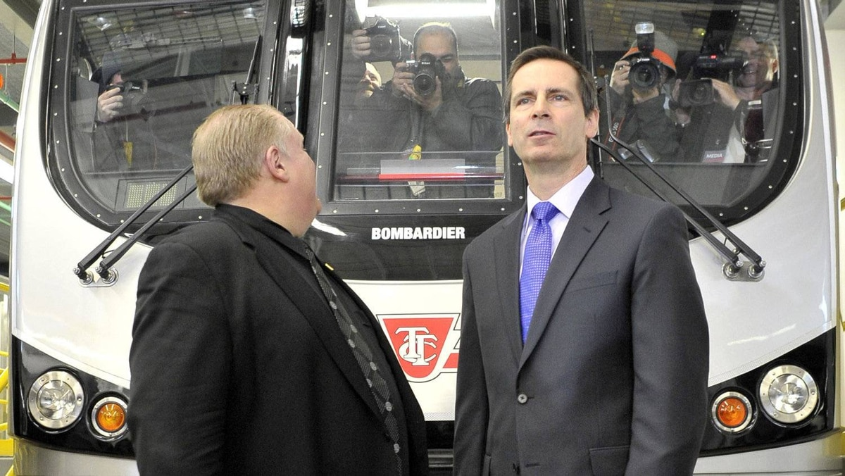 Toronto Mayor Rob Ford looks back at cameramen on a subway cars as Ontario Premier Dalton McGuinty looks forward at another line of cameras following a joint transit funding announcement at the Wilson car yard in Toronto, March 31, 2011.