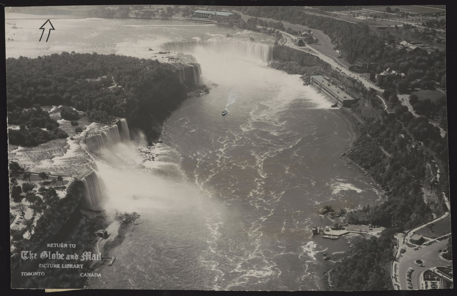 Niagara's world-famed scenic attractions are nearly all displayed in this one comprehensive, low-level air photograph taken from a point directly over the Rainbow Bridge. Part of bridge is at lower left. Clockwise around the picture are: Falls View Park, Niagara Falls, N.Y.; the American Falls (167 feet); Goat Island, with the sightseeing steamship Maid of the Mist in river below; the Canadian Falls (163 feet) and beyond it Hydro intake plant; Table Rock House; the former Ontario Power Co. plant (below cliff); Queen Victoria Park restaurant; Maid of the Mist dock and Clifton incline Oakes Garden Theatre and Memorial Arch on Niagara Blvd. Arrow indicates intake to twin tunnels which will carry 15,000,000 gallons of water a minute under Niagara Falls, Ont., to the giant, new Sir Adam Beck-Niagara Generating Station No. 2 at Queenston. Joint Canada-U.S. construction on remedial works will begin next month to create a more uniform flow, particularly over the 2,600-foot crestline of the Horseshoe Falls which is eroding at the middle, and to contribute to the most effective use of water for power production.
