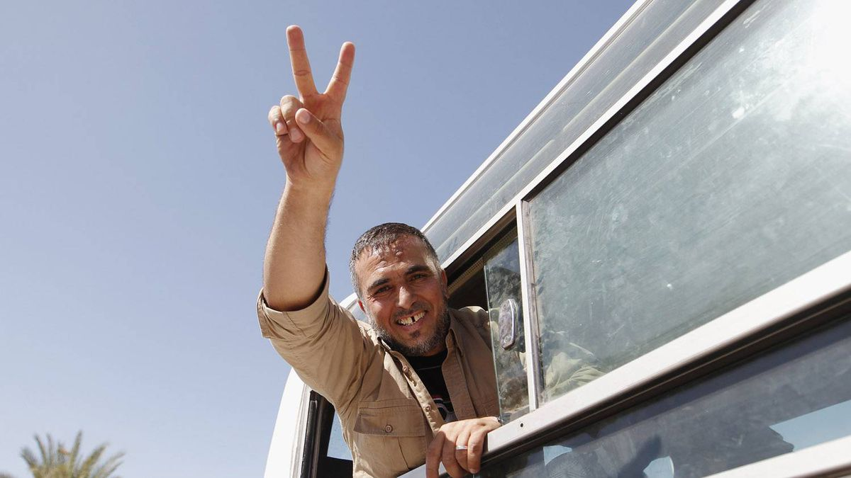 A Palestinian prisoner, released by Israel in exchange for Israeli soldier Gilad Shalit, gestures from a bus as he makes his way through the Rafah border crossing between Egypt and Gaza October 18, 2011.