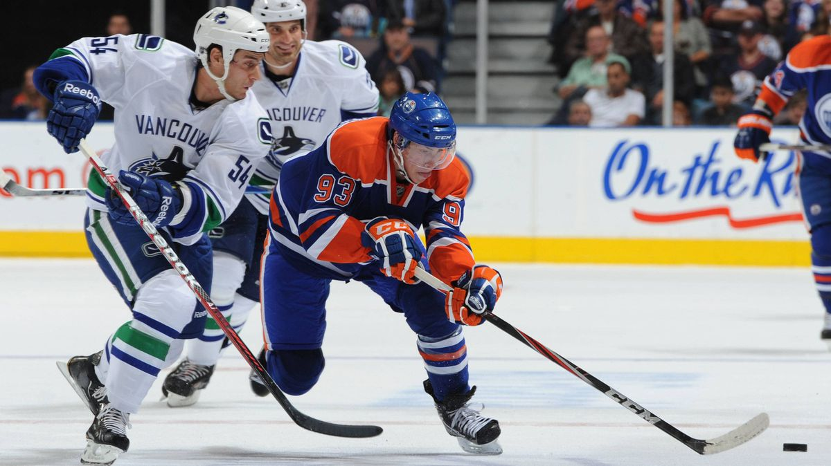 Ryan Nugent-Hopkins of the Edmonton Oilers gets around Aaron Volpatti of the Vancouver Canucks during second-period action in a preseason game Thursday, Sept. 22 at Rexall Place in Edmonton,.