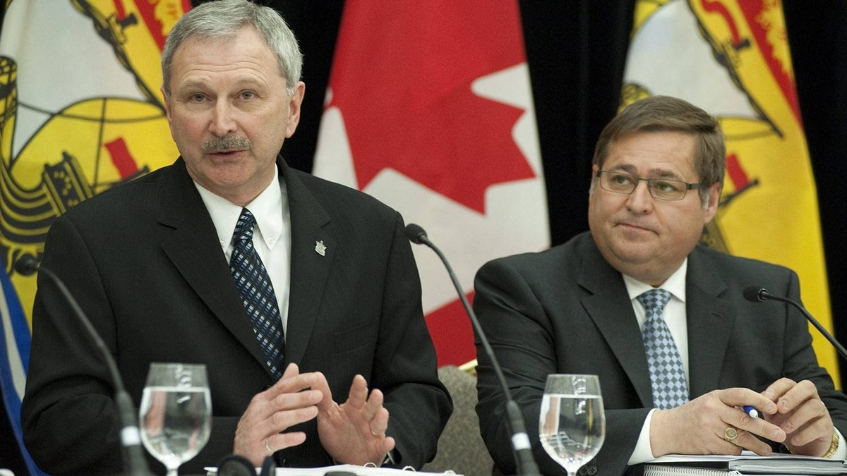 New Brunswick Finance Minister Blaine Higgs (left) and Transportation Minister Claude Williams attend a prebudget news conference March 22.