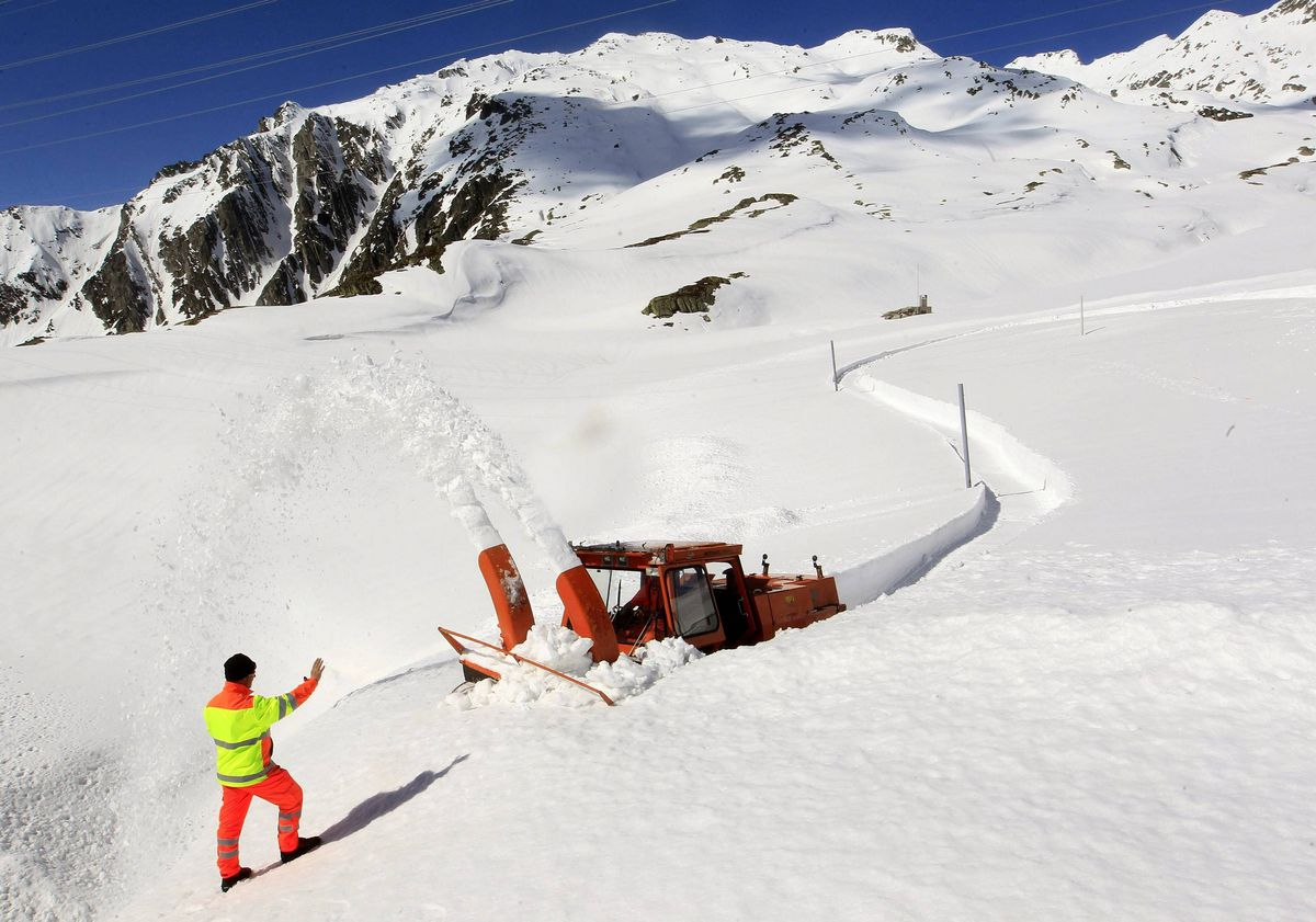 Employee Werner Gnos of the Office for Federal Roads of the Swiss canton of Uri gives instructions to his colleague driving a snow-blower to remove snow at the Sankt Gotthard (Saint Gotthard) mountain pass (2091 metres altitude) in the Swiss Alp.