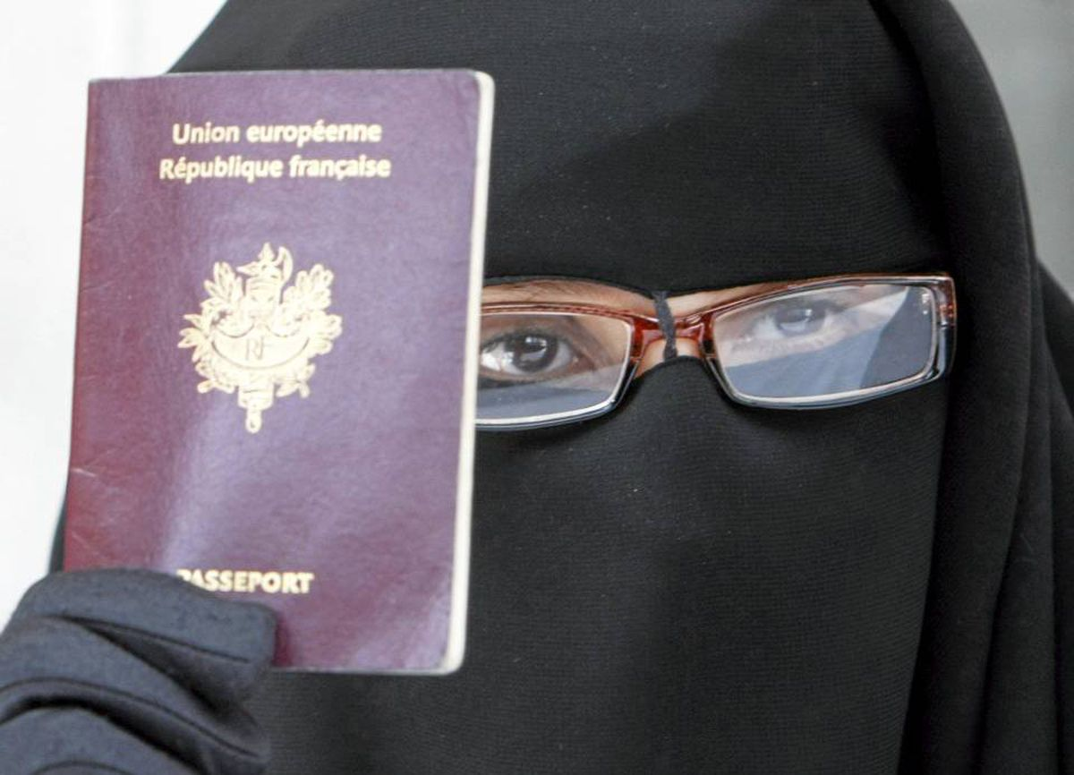 A woman holds her French passport during a press conference in Montreuil, east of Paris, this past May as Muslims speak out against a proposed French law to ban the wearing of burka-style veils in public places.