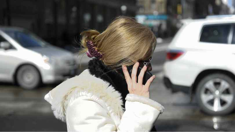Various photos of people using their mobile devices for phoning and texting in downtown Toronto on Feb 22 2011