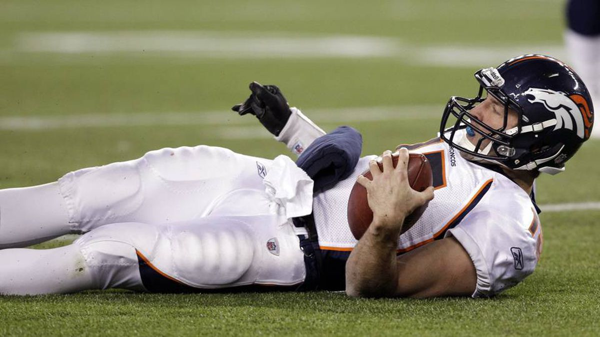 Denver Broncos quarterback Tim Tebow looks up after being sacked by New England Patriots defensive tackle Gerard Warren, not shown, during the first half of an NFL divisional playoff football game Saturday