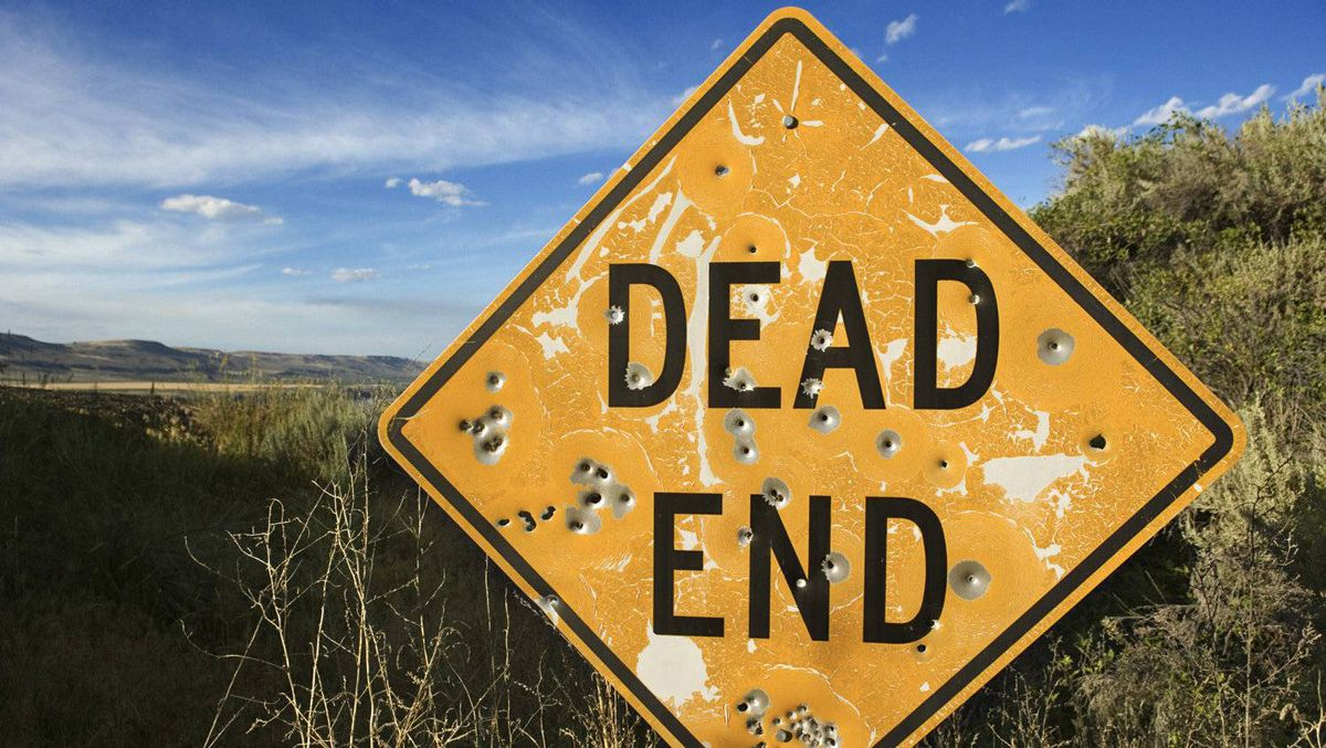 Dead end sign with bullet holes.