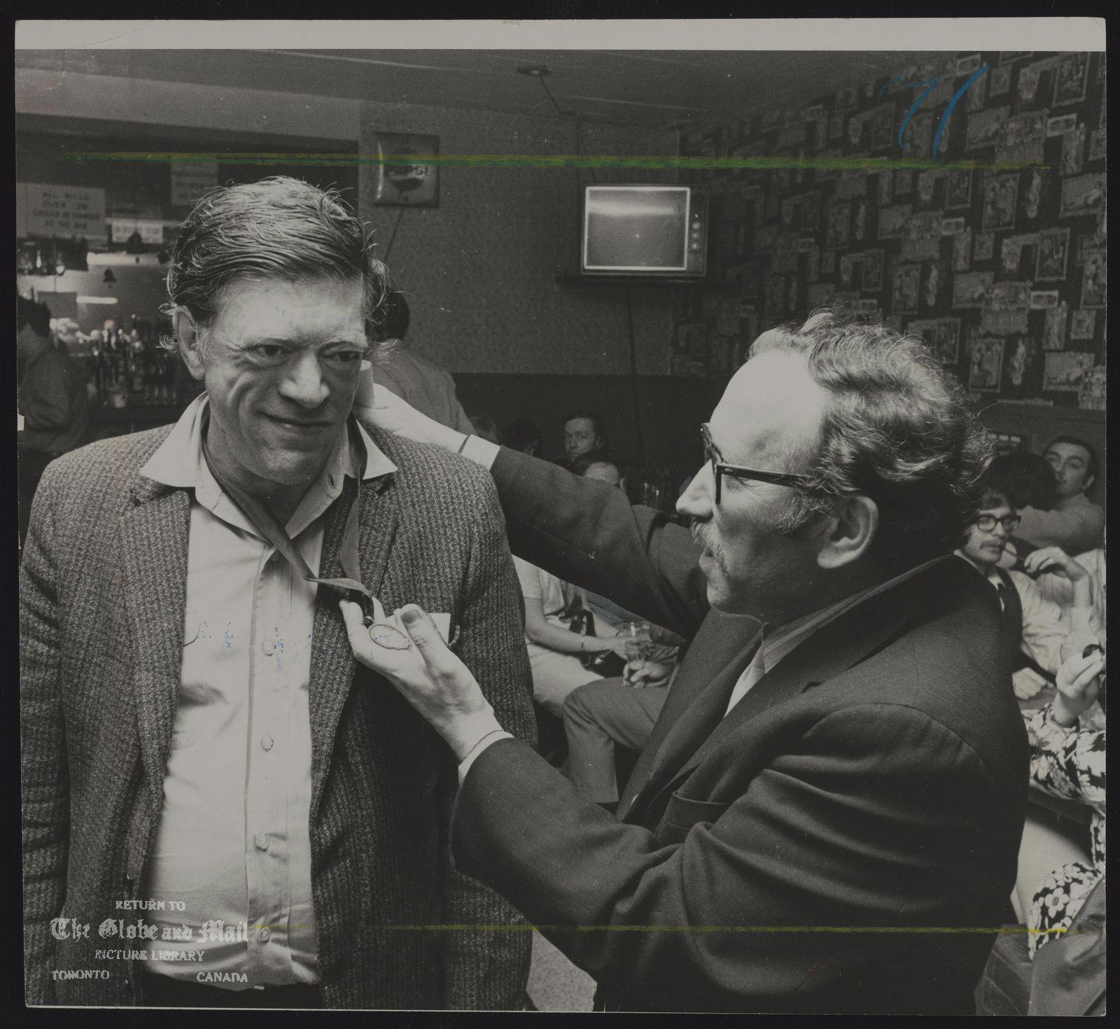 Milton ACORN (Left) Poet receives a medal from poet Eli Mandel