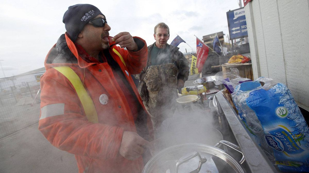 Electro-Motive Canada employees Frank Giampa and John Vandergulick cook up pasta, sauce and meatballs for the workers on the picket line outside the subsidiary of Caterpillar in London on Feb. 8, 2012.