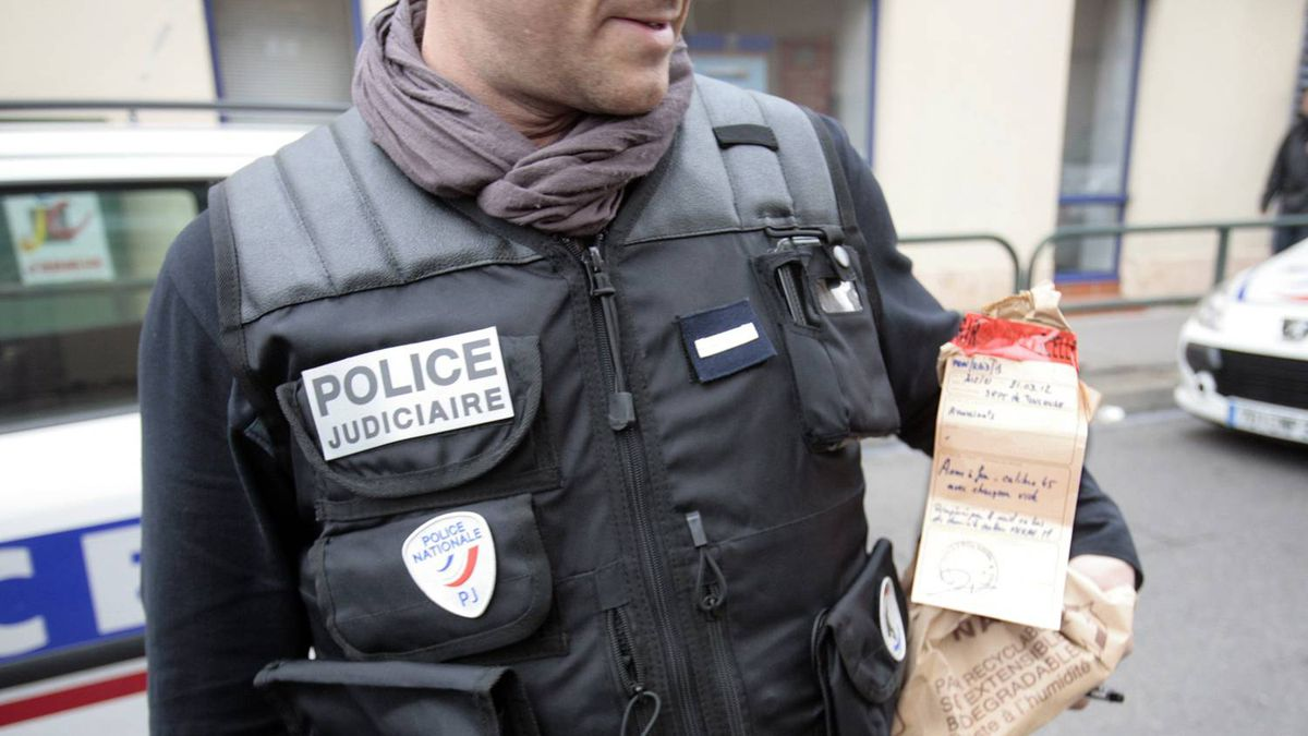 Member of French judiciary police holds bag of sealed evidence near scene during standoff on house in Toulouse